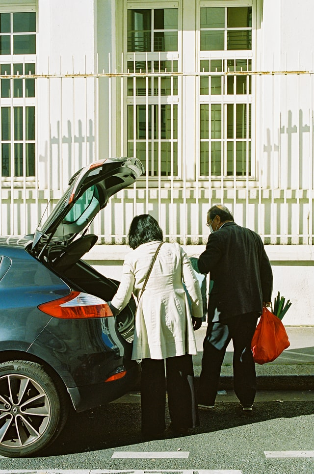 Two people carrying groceries from trunk of car